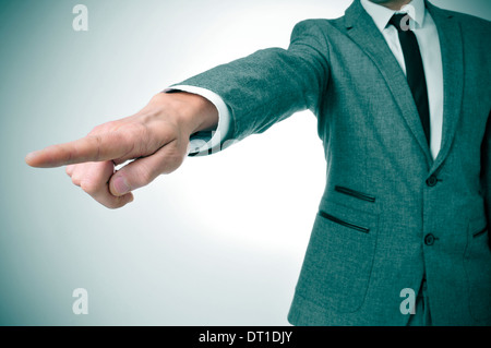a man wearing a suit pointing with the finger the way out - Stock Photo