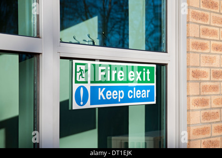 Close up of Fire exit and keep clear sign signs on glass door England UK United Kingdom GB Great Britain - Stock Photo