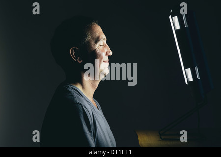 Smiling middle aged man sitting in front of a light therapy box treatment of suffering from seasonal affective disorder - Stock Photo
