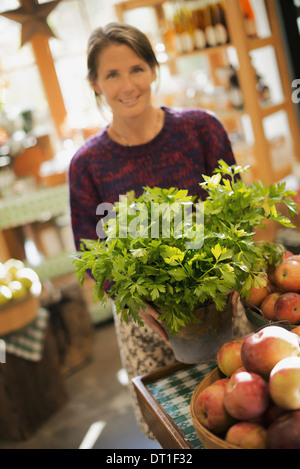 Organic Farmer at Work A woman working on farm stand with a display of fresh produce Green plants and bowls of apples - Stock Photo