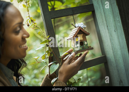 Scenes from urban life in New York City A woman holding a small painted bird house in an enclosure - Stock Photo
