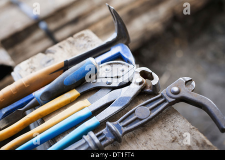 A reclaimed lumber workshop A range of pliers and chisels on a plank of wood - Stock Photo