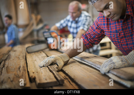 A reclaimed lumber workshop A group of people working A man measuring and checking planks of wood for re-use and - Stock Photo