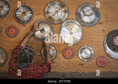 A reclaimed lumber workshop A man reaching up to a storage board for circular saw blades to replace a blade - Stock Photo