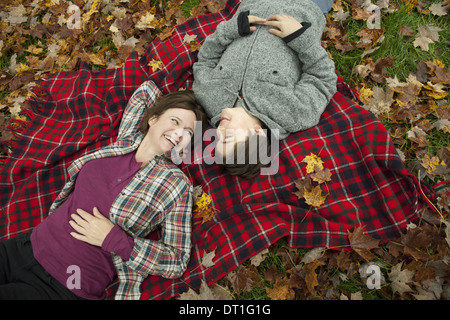 Two people a woman and a child lying on a red tartan picnic blanket looking upwards - Stock Photo