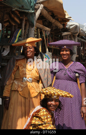 Three Herero tribe women in Namibia,wearing their traditional German era inspired Victorian dress and  cow-horn - Stock Photo