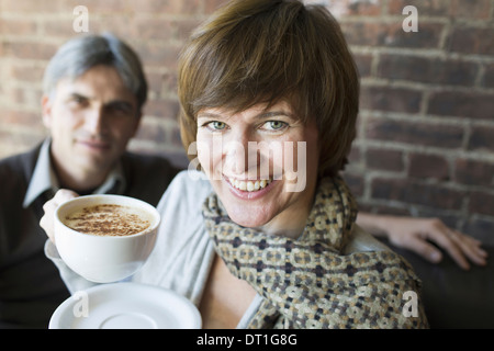 Two people sitting in a coffee shop A man and woman holding white china cups of cappuccino coffee - Stock Photo
