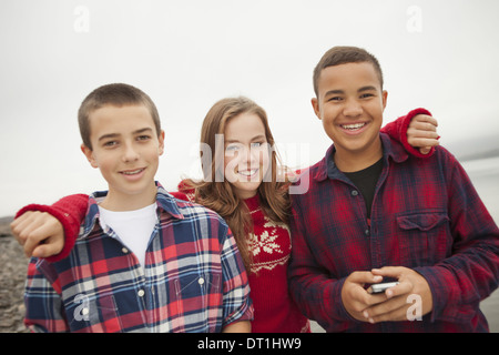 A day out at Ashokan lake Three teenagers boys and a girl in a row Friends - Stock Photo
