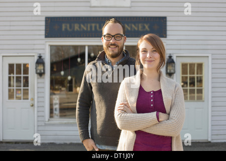 A man and woman standing outside a storefront on a street A couple running an antique shop - Stock Photo