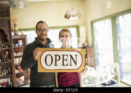 Two people standing in a store full of antique objects a couple running a business Holding a large sign saying OPEN - Stock Photo