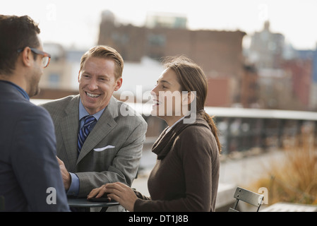 Three people standing in an open space between city buildings talking to each other Two men and a woman - Stock Photo
