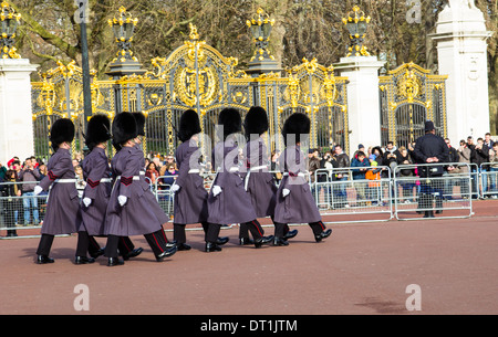 LONDON, UK, 2ND FEB 2014: Royal Guard Soldiers marching outside Buckingham Palace in front of crowds of people. - Stock Photo