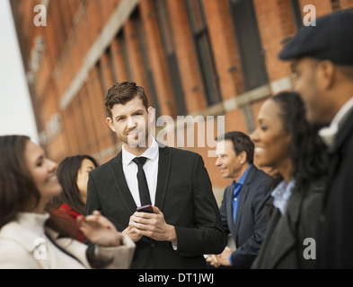 using mobile phones and talking to each other Men and women - Stock Photo