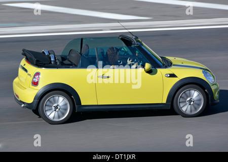 Two door BMW Mini Cooper open top convertible car with woman driving on motorway M25 motorway Essex England UK