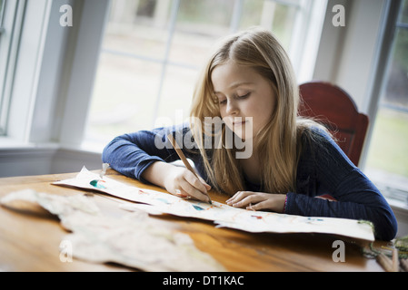 A family home A young girl sitting at a table drawing on a large piece of paper Holding a pencil - Stock Photo