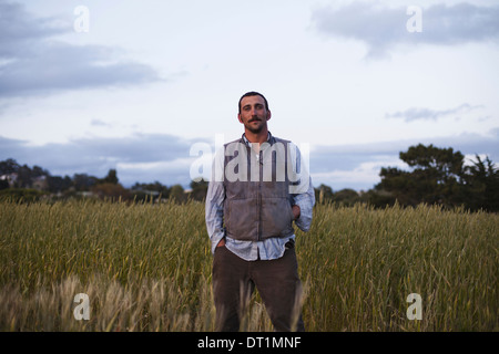 A man standing by a field of growing cereal crop at the social care and work project the Homeless Garden Project - Stock Photo