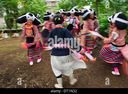 Long Horn Miao girls in traditional costumes celebrating Flower Dance Festival, Longjia village, Guizhou Province, - Stock Photo