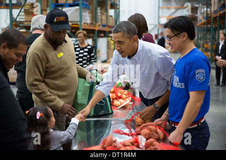 USA Washington DC Community Volunteers At A Soup Kitchen; US President  Barack Obama Shakes Hands With A Young Girl While He, First Lady Michelle