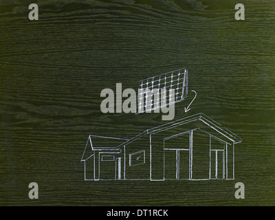 A line drawing image on grained wood A green building project a house with solar panels for the roof - Stock Photo