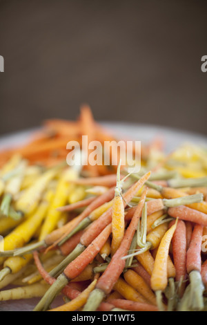 Organic vegetables in a dish Cooked orange yellow and pink heritage baby carrots Farm stand produce - Stock Photo