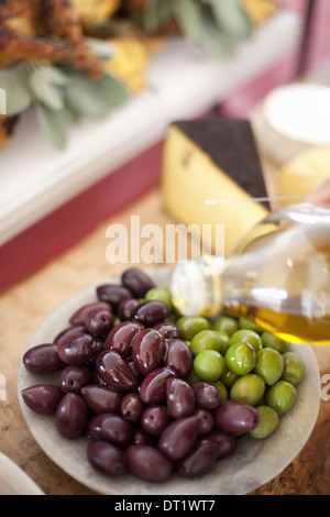 fresh organic vegetables Green and black olives drizzling of olive oil from a bottle Prepared farm stand foods for - Stock Photo