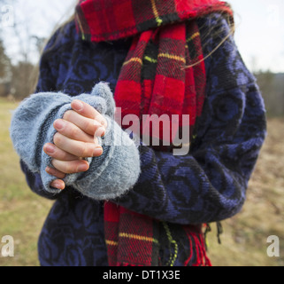 A woman in a tartan scarf and knitted woollen mitts keeping her hands warm in cold weather - Stock Photo