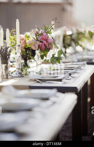 A formal wedding breakfast table laid for a feast Fresh flowers in the centre - Stock Photo