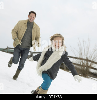 A man chasing a young girl in the snow Farm in winter - Stock Photo