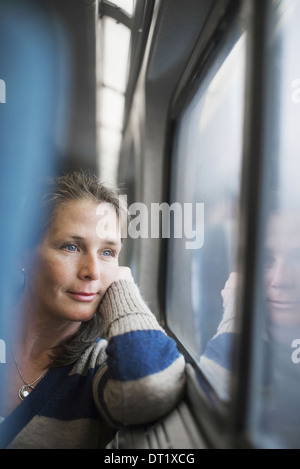 A woman sitting at a window seat in a train carriage resting her head on her hand Looking into the distance - Stock Photo