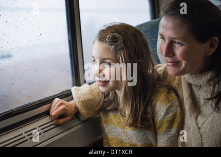 A man and a young girl sitting beside the window in a train carriage looking out at the countryside Smiling in excitement - Stock Photo