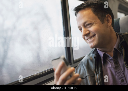 A mature man sitting at a window seat on a train holding his mobile phone Smiling and looking in the distance - Stock Photo