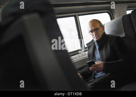 A mature man sitting by a window in a train carriage using his mobile phone keeping in touch on the move - Stock Photo