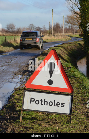 four wheel drive vehicle passing warning sign of potholes on country road yorkshire united kingdom - Stock Photo
