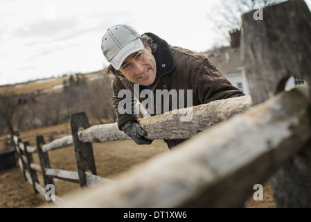 A man leaning against a post and rail fence on a farm in winter - Stock Photo