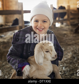 A child in the animal shed holding and stroking a baby goat - Stock Photo