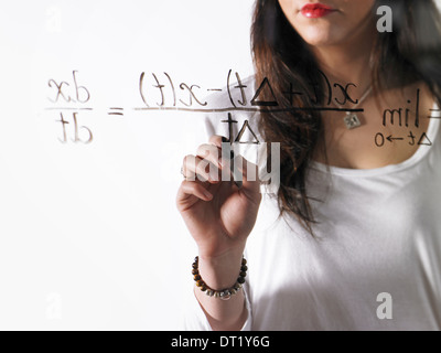 A young woman writing a mathematical equation with black marker on a clear see-through surface - Stock Photo