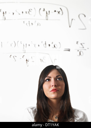A young woman writing a mathematical equation with black marker on a clear see-through surface and standing back - Stock Photo