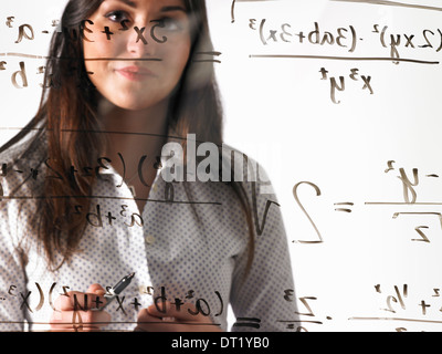A young woman looking at a mathematical equation written out with black marker on a clear see-through wall - Stock Photo