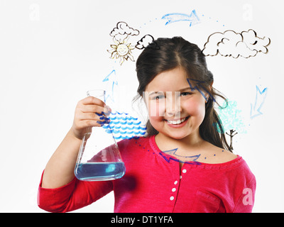 A young girl holding a conical flask of blue liquid in front of an evaporation cycle illustration drawn on a clear - Stock Photo