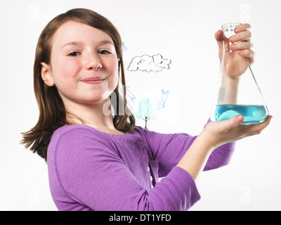 A young girl holding a conical flask of blue liquid in front of an evaporation cycle illustration on a clear surface - Stock Photo