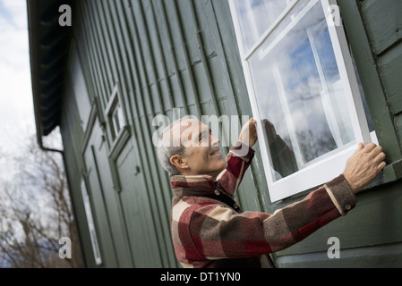 An organic farm in winter Maintenance A man holding a storm window panel against the window frame - Stock Photo
