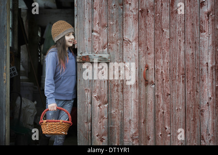 An organic farm in upstate New York in winter A girl in a barn doorway with a basket - Stock Photo