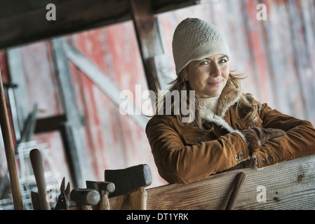 A woman in a sheepskin coat A row of hand tools hanging on a post - Stock Photo
