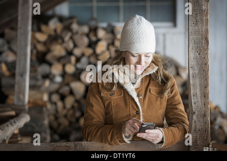 An organic farm in upstate New York in winter A woman in sheepskin coat and woollen hat using a cell phone - Stock Photo