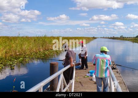 Florida Fort Ft Lauderdale Everglades Alligator Alley Black woman man fishing water - Stock Photo