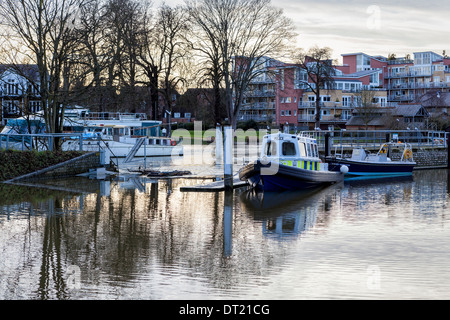 Police patrol boat on the Thames river at Teddington lock and weir at dusk, Greater London, UK - Stock Photo