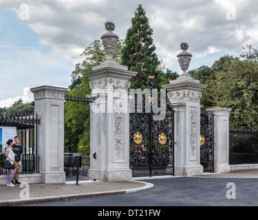 Couple at ornate main gates of Royal Botanic Garden, Kew Gardens, London, UK - Stock Photo