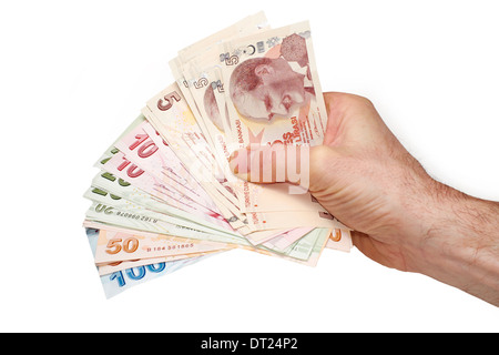 A hand holding a mixture of Turkish Lira Currency, on a white background. - Stock Photo