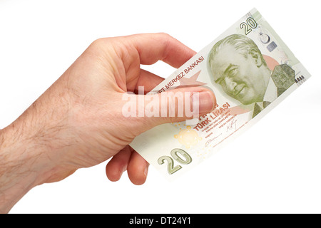 A hand holding a Turkish 20 Lira note, on a white background. - Stock Photo