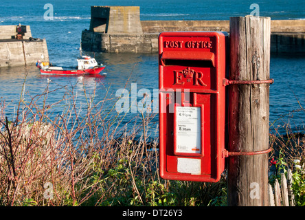 Bright Red British Post Box by the Harbour in the village of Craster, Craster, Northumberland, England, UK - Stock Photo